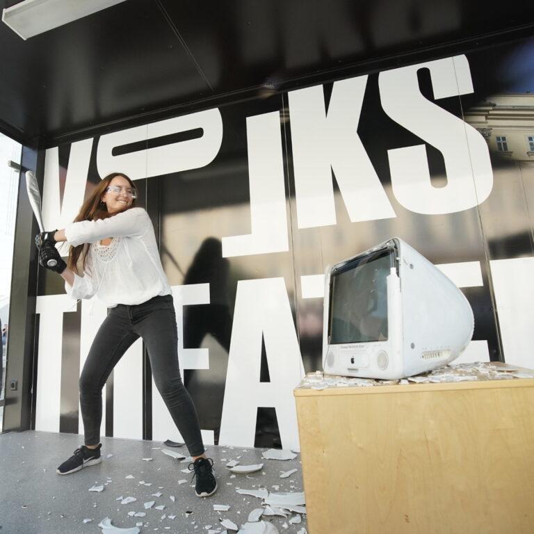 Journalistin Amra Durić holt im Wutraum des Volkstheaters aus, um einen Mac mit einem Baseballschläger zu zerstören.