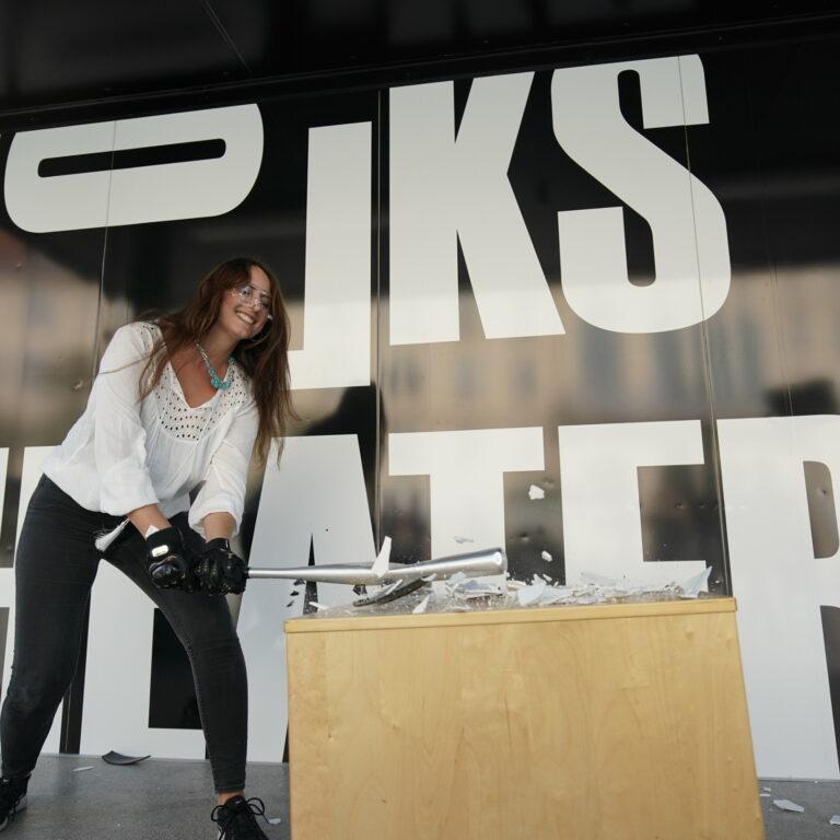 Journalistin Amra Durić zerstört im Wutraum des Volkstheaters lächelnd einen alten Mac