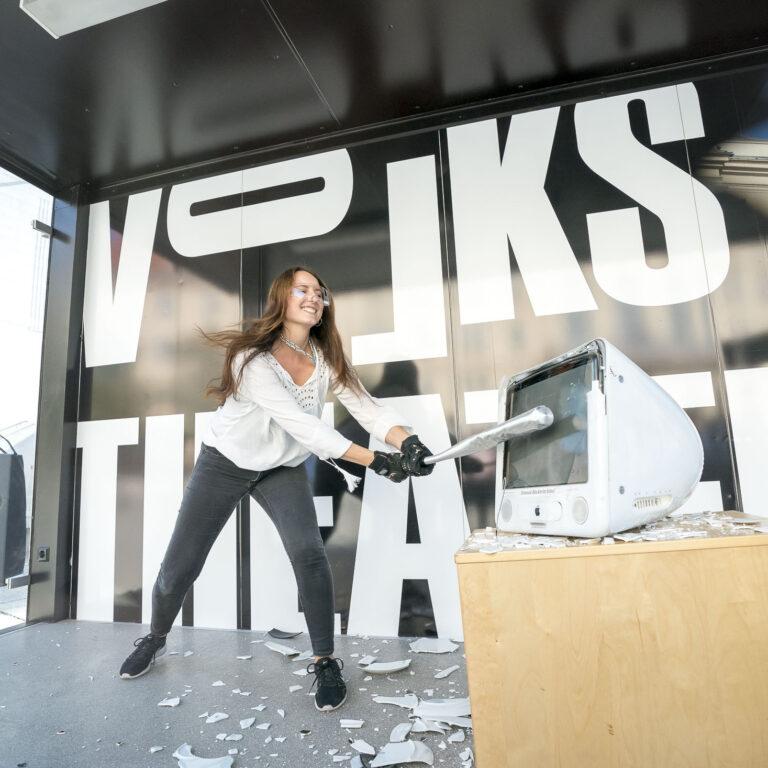Journalistin Amra Durić schlägt im Wutraum des Volkstheaters mit einem Baseballschläger auf einen alten Mac.